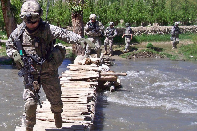 """Soldiers navigate across a creek during a dismounted patrol in the Nerkh Valley, Afghanistan, June 4, 2009. Thursday, Defense Secretary Robert M. Gates said a new """"intermediate"""" command set for Afghanistan will allow the commander to concentrate on day-to-day tactical events across the country. The pictured Soldiers are assigned to Battery B, 4th Battalion,25th Field Artillery Regiment on Forward Operating Base Airborne."""