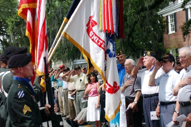 Veterans salute the Colors at the D-Day anniversary ceremony outside Post 135 on June 6. The veterans mingled with 3rd ID Soldiers at a luncheon following the ceremony.