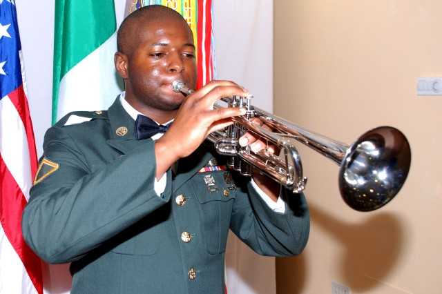 """Pfc. Marcus Cyriaque, 511th Military Police Company, plays mess call on his trumpet during the Camp Darby Army Birthday ball. The U.S. Army Garrison Livorno Command Sgt. Maj. Felix Rodriguez learned that the young Soldier liked to play the trumpet and asked him to learn how to play """"Call to Mess"""" for this special occasion."""