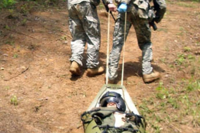 "Capt. Robert Killian and 1st Lt. Grant Barge use an improvised litter to evacuate a ""casualty""  during the 26th annual Best Ranger competition. Theirs was the only Fort Polk team to complete the competition."