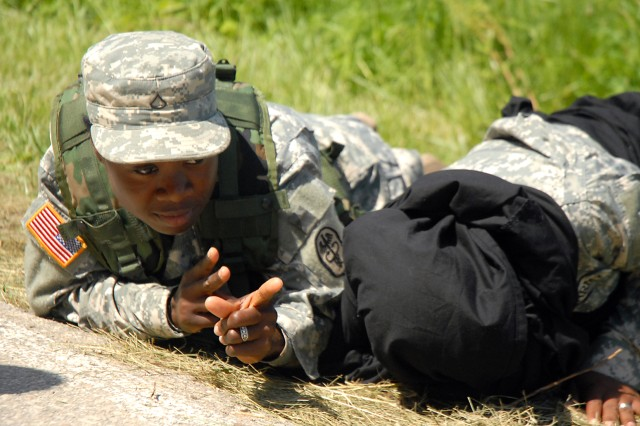 Combined Arms Center Soldier of the Year competitor Pfc. Dorcas Abotchie, of Medical Department Activity at Fort Knox, Ky., mimics responding to enemy fire alongside a subject she was searching, portrayed by Spc. Brishette Coulter, of the 40th Military Police Battalion, at a warrior task station June 3 off Sheridan Drive, Fort Leavenworth, Kan.