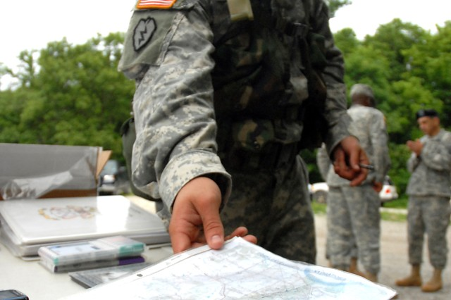 Staff Sgt. Leon Butler, of the 399th Army Band at Fort Leonard Wood, Mo., turns in his day land navigation materials after completing the course during the Combined Arms Center NCO of the Year June 3 near Heritage Trail, Fort Leavenworth, Kan.