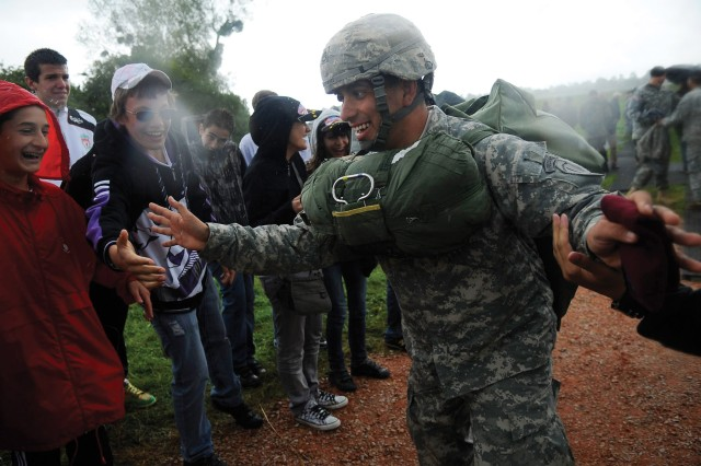 SSG Emmanuel Rodriguez, an airborne instructor with the 1st Battalion (Airborne), 507th Parachute Infantry Regiment, is greeted by local villagers after completing the jump. Rodriguez, along with 33 Soldiers from the battalion, toured historic World War II battlefields in France during a weeklong trip.