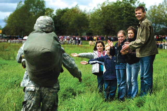 Local French children congratulate an American paratrooper after he successfully jumped from a C-130 onto La Fiere Drop Zone in FranceAca,!a,,cs Normandy region during a June 7 airborne operation commemorating the June 6, 1944 D-Day invasion.