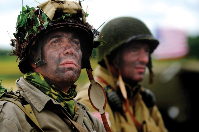 A re-enactor dressed in a WWII U.S. Army uniform watches as U.S. Army Airborne Soldiers land.