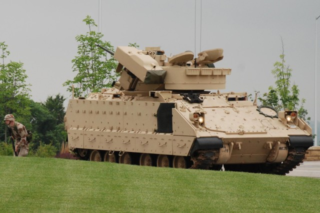 """One 1st Infantry Division soldier runs out of a M2 Bradley Fighting Vehicle to join other period-dressed soldiers from various conflicts in the Army's history during the Army's 234th birthday and the 1st Inf. Div.'s 92nd birthday celebration June 11 in front of division headquarters. (1st Inf. Div. Public Affairs photo by Jordan Chapman)"""""""