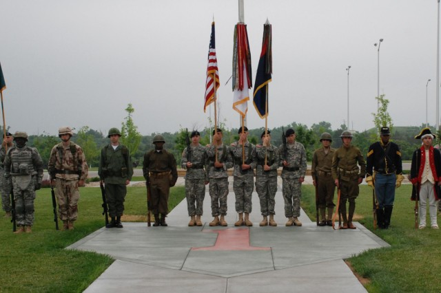 Soldiers of 1st Infantry Division dressed in period military uniforms stand at attention around the Color Guard during the Army's 234th birthday and 1st Inf. Div.'s 92nd birthday celebration June 11 on the parade field in front of division headquarters. (1st Inf. Div. Public Affairs photo by Jordan Chapman)""
