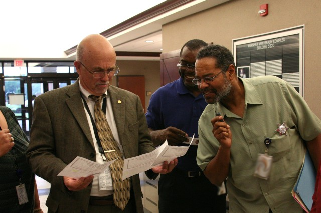 Prisoner Bill Congo looks over three of four of his arrest warrants during U.S. Space and Missile Defense Command/Army Forces Strategic Command's Jail Day on June 10, while Thaddeus Brown and Andrew Johnson look over Congo's shoulder. Congo set a record for delinquency with his warrants. Congo is the director of Public Affairs, Brown works for the Future Warfare Center, and Johnson is an engineer.