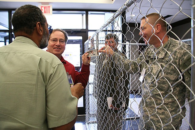 Prisoner Lt. Col. Rob Phillips earns a longer stay in jail when he attempts to pass a counterfeit bill to Sheriff Phil Patterson during U.S. Space and Missile Defense Command/Army Forces Strategic Command's Jail Day on June 10. Patterson then asked Thaddeus Brown if he thought the bill was indeed fake. Phillips is the commanding general's executive officer, Patterson is a general engineer, and Brown works at the Future Warfare Center.