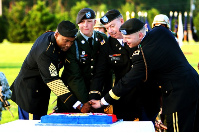 Cutting a cake to celebrate the Army's 234th birthday, Maj. Gen. Tony Cucolo (right) and Division Command Sgt. Maj. Jesse Andrews (Left) carry on an old tradition along with Fort Stewart's youngest and oldest Soldier at Cottrell Field, June 12.