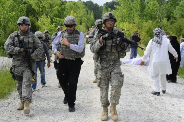 U.S. Agency for International Development field program manager Eric Florimon, second from left, is led to safety by members of the provincial reconstruction team bound for Afghanistan's Nangahar province, June 9, 2009, during an exercise at Camp Atterbury, Ind.