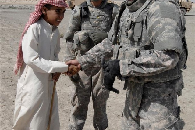 Staff Sgt. Michael A. Mendez, the medical noncommissioned officer for the 167th Combat Sustainment Support Battalion, greats a young boy from a Bedouin family during a Civil Military Operation in Dhi Qar province, Iraq June 3.