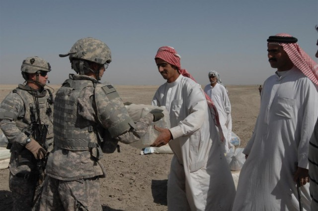 Members of the 167th Combat Sustainment Support Battalion hands a case of bottled water to a Bedouin family during a Civil Military Operation in Dhi Qar province, Iraq June 3.
