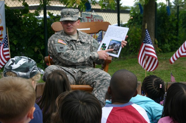 "ANSBACH, Germany -- Sgt. Jose Fonseca, D Company of the 2-159th Aviation Battalion, reads ""The Army Story,"" to about 80 children at the U.S. Army Garrison Ansbach Storck Barracks Child Development Center playground June 12 in celebration of the Army's 234 birthday."