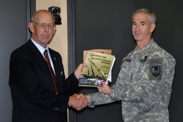 "Lt. Gen. Kevin T. Campbell, commanding officer, U.S. Army Space and Missile Defense Command/Army Forces Strategic Command takes possession of the two-volume study ""History of Strategic Air and Ballistic Missile Defense"" during a book presentation ceremony on June 11."