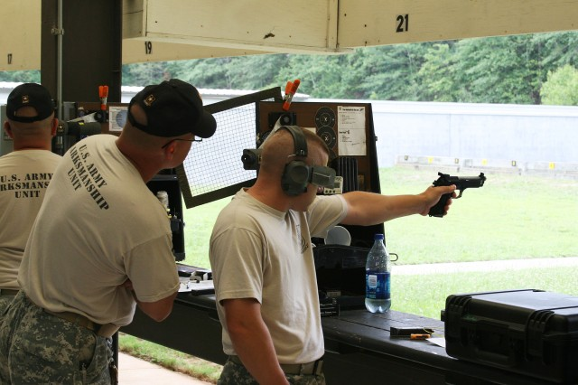 Staff Sgt. Adam Sokolowski, U.S. Army Marksmanship Unit, concentrates during a team match June 10 at Phillips Range, Fort Benning, Ga., as team member Staff Sgt. James Henderson looks on in support. The Soldiers were taking part in the 50th Interservice Pistol Championships.