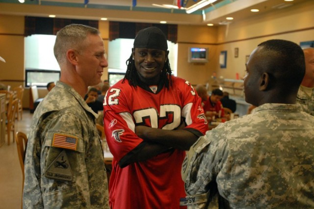 Jerious Norwood, a running back for the Atlanta Falcons (middle), speaks with Col. Pete Jones, the commander of the 3rd Heavy Brigade Combat Team, 3rd Infantry Division (left), and Lt. Col. Robert Ashe, the commander of the 2nd Battalion, 69th Armor Regiment (right), during the Atlanta Falcons visit to Kelley Hill on Fort Benning, Ga., June 8. Ten players and 10 cheerleaders from the Falcon's dance team traveled to Fort Benning to talk with the Soldier's of the 3rd HBCT and sign autographs.