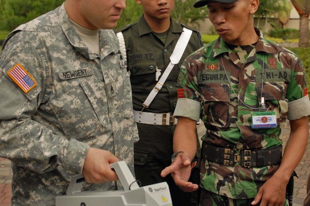 Staff Sgt. Mark Newgent, a native of Pearl City, Hawaii and force protection specialist assigned to the 9th Mission Support Command shows Tentara Nasional Indonesia Angkatan Darat, or Indonesian Army, Senior Serviceman Teguh-Pa Pojianto, an explosive ordnance specialist  how to check for explosives residue outside a hotel in Bandung, Indonesia, June 12.