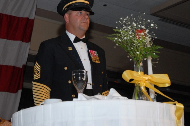 Command Sgt. Maj. Joseph P. Zettlemoyer, command sergeant major, USARPAC, demonstrates the meaning of each item on the Fallen Comrade Table during the 234th Army Birthday Celebration at the Hilton Hawaiian Village.  The table symbolizes those individuals missing from the celebration and honors their sacrifice and devotion to a grateful nation.