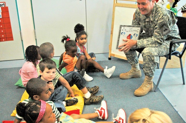 """Maj. Gen. Terry Wolff, 1st Armored Division commander, reads """"Sam, the Army Dog"""" to children at the Wiesbaden Army Airfield Child Development Center June 12."""