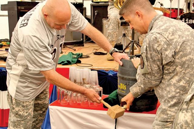 Lt. Gen. Kenneth E. Hunzeker, V Corps commander, and Lt. Col. Derek Rountree, U.S. Army Garrison Baumholder commander, tap the first beer keg during the welcome home celebration.
