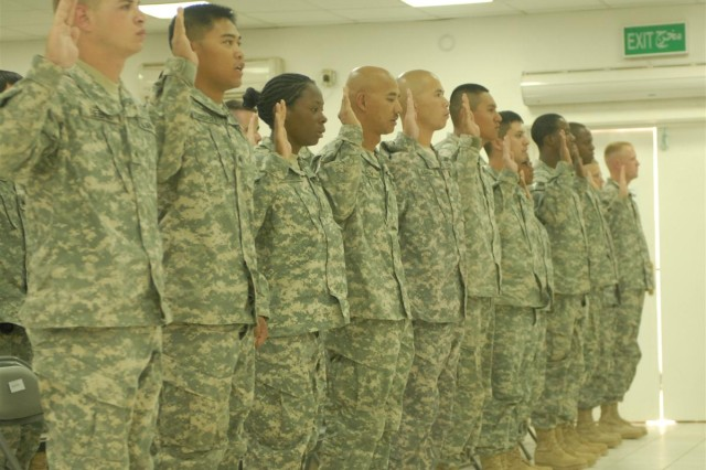 Soldiers of the 398th Combat Sustainment Support Battalion raise their right hand and repeat the noncommissioned officer's charge during an NCO induction ceremony at Camp Liberty, Iraq June 2.