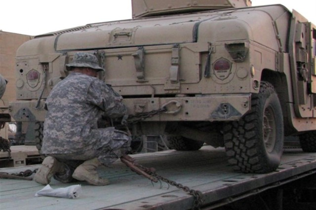 A Soldier from the 1538th Transportation Company, Indiana Army National Guard, secures a humvee on a trailer while properly demonstrating load procedures and preparing for transport across Iraq during a unit training session at Camp Taji, Iraq.