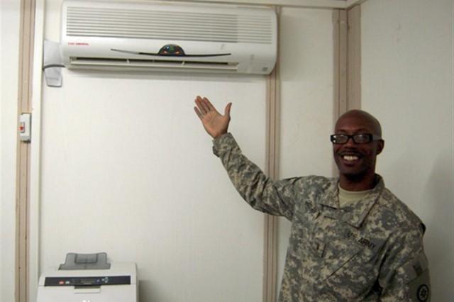 "Chief Warrant Officer 3 Kenneth Hosby, 351st Ordnance Co., 30th Combat Sustainment Support Battalion, 16th Sustainment Brigade, shows off his new office and air conditioning unit. Hosby will manage the flow of ammunition, and make decisions regarding the location of ammunition assets throughout ""Scorpion"" ammunition supply point."