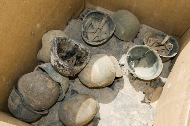 A box of helmets collected from the trash at Joint Base Balad, Iraq, awaits delivery to the Defense Reutilization and Marketing Office yard at JBB May 15.  Under Department of Defense policy, throwing away such items is considered waste and abuse of government property.