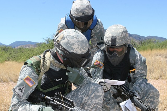 """Spc. Anthony Bennett, (left), Company B, 304th MI Bn and Sgt. Nhan Huynh, (right), Company B, 304th MI Bn send a simulated """"Unexploded Ordinance"""" report, while evaluated by Sgt. 1st Class Paul Sunseri, (center), Company C, 304th MI Bn. 304th Soldiers were subjected to multiple warrior tasks during the training, and critiqued during a process called """"after action reviews"""" each time."""
