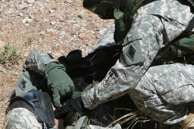 "A 304th Soldier practices how to evaluate a casualty on a ""wounded"" squad member. Correctly performing this action is one of the Army's 40 Warrior Tasks."
