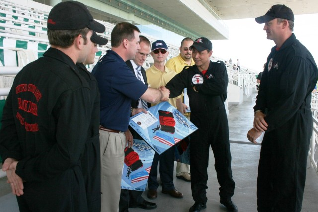 "Staff Sgt. Dewey Vinaya, Assistant Team Leader, USASOC 'Black Daggers' Parachute Demonstration Team, presents a Black Daggers coin to Tony Enrietto, one of the Co-Hosts of ""Salute to the Troops"" Day at the Arlington Park Racetrack on Sunday, 14 June, 2009. Also presented with team coins, from left to right, next to Enrietto are: Wesley Ward, Mgr. of Marketing and Advertising for Arlington Park; Ross Docksey, Chairman, USO of IL and Geoff Gephart, USO Project Officer for the Parachute Demonstration in Arlington Heights, IL."