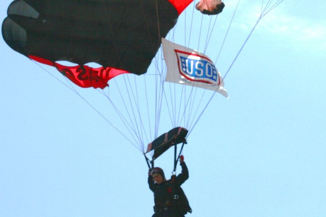 "Sgt. Tony Galusha, USASOC 'Black Daggers,' Parachute Demonstration Team, Fort Bragg, NC, jumps in the USO Flag onto the Arlington Park Race Track, Arlington Heights, IL, during the ""Salute to the Troops"" Day, honoring our military and co-hosted by the USO of Illinois."