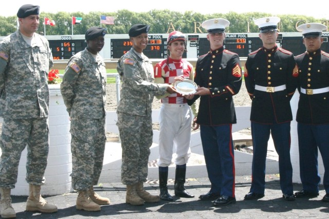 Soldiers and Marines help present the winning Jockey his silver plate during the USO Salute to the Troops, Trophy Presentation at Arlington Park Racecourse. Soldiers pictured from left to right are: PV2 Kiriakos Stafilas, USAREC Mount Prospect, IL Recruiting Station; Pvt. 1st Class, Alicia Martinez Lambey, C Co. 58th Trans 24T Ft. Leonard wood Missouri and Pvt. 1st Class, Errika Stiltner, 933rd MP Company, ILARNG in Waukegan, IL.