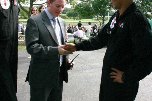 "Nick Demonte, Marketing and Operations Coordinator for Arlington Park, is presented with a USASOC Black Daggers coin for setting up Army assets and helping host the Parachute Demonstration Team from Fort Bragg. NC. The Paratroopers were at the racetrack in Arlington Heights, IL for ""Salute to the Troops"" Day, on Sunday, 14 June, 2009, which also happened to be the Army's 234th Birthday. Presenting the coin is Staff Sgt. Dewey Vinaya and standing with him is Sgt. 1st Class, Dave Rose, Team Leader for the Black Daggers."