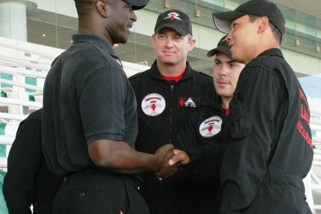 "Staff Sgt. Dewey Vinaya and fellow team members of the USASOC 'Black Daggers' Parachute Demonstration Team, Fort Bragg, NC, present MSG (ret.) Jay Johnson, with their coin, to thank him for officially narrating their demonstration at Arlington Park Racetrack on Sunday, 14 June, 2009. The Parachute Demonstrators were in Arlington Heights, IL for ""Salute to the Troops"" Day, co-hosted by the USO of IL and Arlington Park."