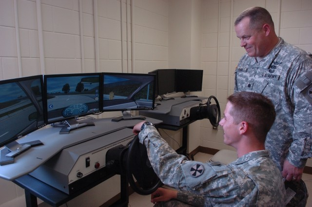 Pvt. Rand Burd, 4-58th Airfield Operations Battalion, practices his skills at a driving station at the new USAG-Humphreys Army Traffic Safety Facility, which opened here June 2. Watching is Lt. Col. Joel Kain, commander of 4-58th AOB.