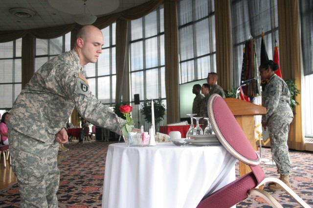 Sergeant. Stephen Hicks, West Point Medical Dept. Detachment, places the first slice of the Army's birthday cake on the Fallen Comrades table during the West Point Army Birthday celebration on June 16.  West Point marked the Army's 234th birthday with a ceremony that included a promotion, re-enlistment and a tribute to patriotism.  (Photo by Master Sgt. Dean Welch/DComm)