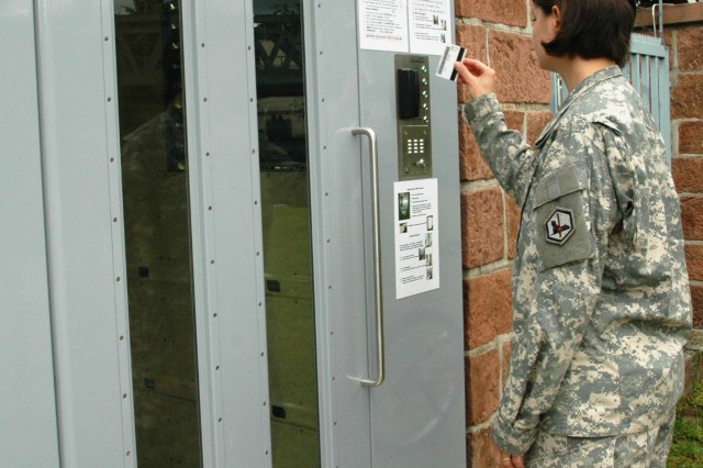 """Sgt. Cheryl Mancill swipes her Common Access Card through the reader to gain admission to the gate. The instructions for using the gate are posted at the entrance. The intercom button, labeled """"Call,"""" is below the card reader."""
