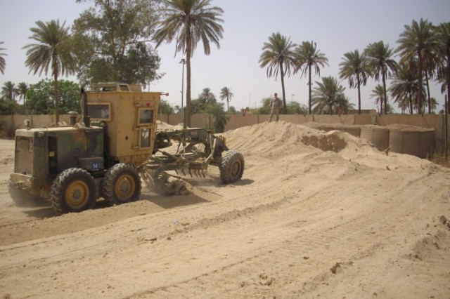 BAGHDAD - A heavy equipment operator from Equipment Platoon, 46th Engineer Combat Battalion (Heavy), serving with the 225th Engineer Brigade, uses a grader to spread sand and dirt from old Hescos barriers.  The sand was used to level out the ground at the Helicopter Landing Zone.