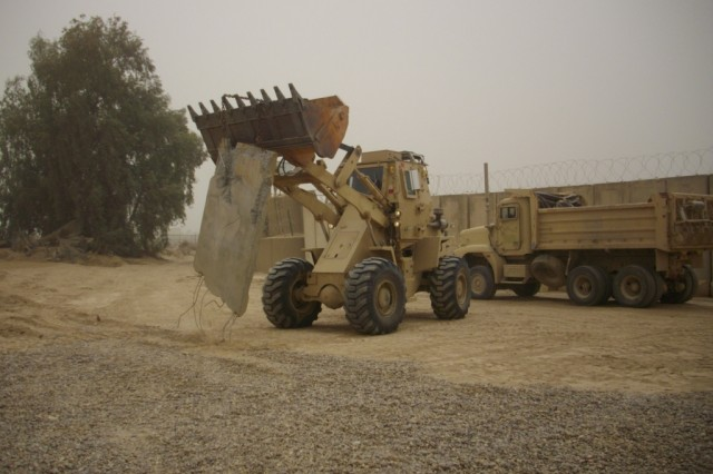 BAGHDAD - Heavy equipment operators from the 46th Engineer Combat Battalion (Heavy), 225th Engineer Brigade, use a loader and a dump truck to remove debris from one of the ranges.  This range was so badly damaged it had to be completely rebuilt.