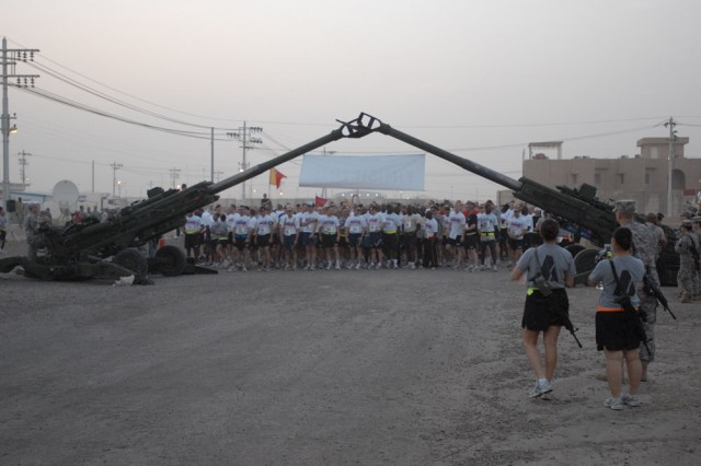 CAMP TAJI, Iraq - Under the arch of artillery cannons, Soldiers ready themselves along the starting line in the early morning hours to begin the 108th Field Artillery Memorial Day Marathon.  The Los Angeles Marathon organizers sponsored the race providing banners, t-shirts and awards.