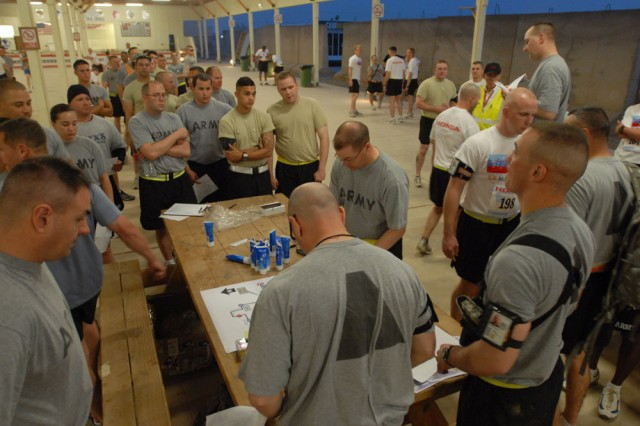 CAMP TAJI, Iraq -Soldiers gather at the registration area in the early morning hours to begin the 108th Field Artillery Memorial Day Marathon.  The Los Angeles Marathon organizers sponsored the race providing banners, t-shirts and awards.