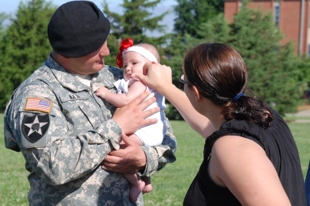 """Sgt. Eric Math of the 41st Engineer Company, 1st Engineer Battalion, 1st Brigade, holds his daughter, as his wife shares in the moment after the """"Bulldawgs"""" deployment ceremony June 16 at Fort Riley's Custer Hill Parade Field."""