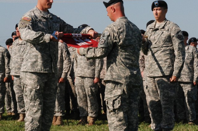 Capt. Reginald H. Rice (left), company commander of the 41st Engineer Company, 1st Engineer Battalion, 1st Brigade, and 1st Sgt. David Hopkins (center) roll up the company colors so it may be cased while they are deployed to Afghanistan for one year during a deployment ceremony June 16 at Fort Riley's Custer Hill Parade Field.