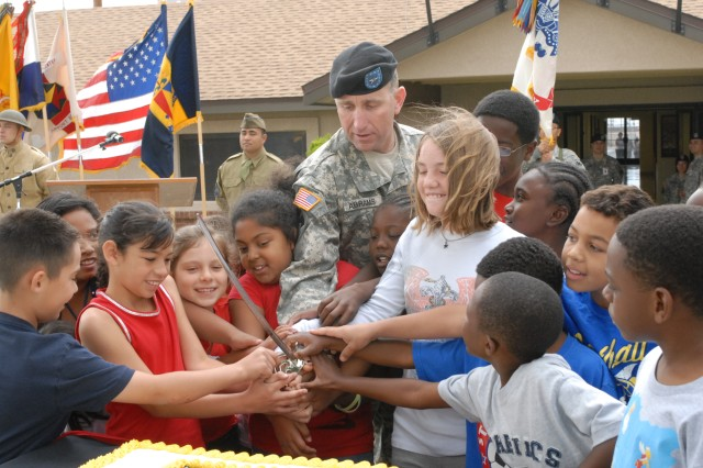 "Fort Irwin/National Training Center Commander Brig. Gen. Robert ""Abe"" Abrams prepares to cut the post's Army birthday with help from some children from the Fort Irwin CYSS program on June 10."