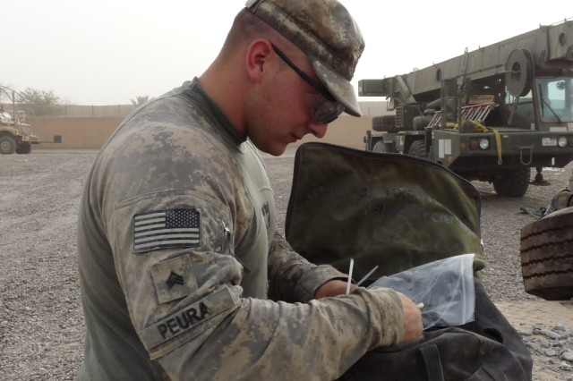 BAGHDAD - Sgt. Jason Peura, from Montgomery, Ill., a light-wheeled mechanic with the 46th Engineer Combat Battalion (Heavy), searches through his tool bag for the right tool to fix the brakes on a trailer. Peura has been in the Army for seven years.