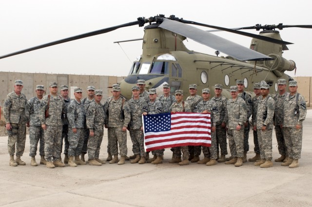 CAMP TAJI, Iraq-Senior warrant officers from the 1st Air Cavalry Brigade, 1st Cavalry Division, Multi-National Division-Baghdad, and 4th Combat Aviation Brigade, 4th Infantry Division, stand together in front of a CH-47F Chinook helicopter, May 24, on the airfield at Camp Taji, Iraq. The warrant officers met to add up the amount of hours flown and years served in their careers.