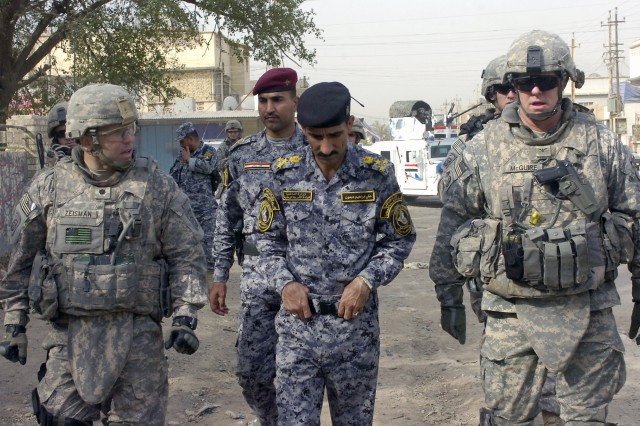 BAGHDAD - Lt. Col. Louis Zeisman (left), of Fayetteville, N.C., along with Iraqi Brig. Gen. Ali Ibraheem Dabown (center), commander of the 8th National Police Brigade, 2nd NP Division, and Col. Timothy McGuire (right), of Alamo, Calif., commander of the 3rd Brigade Combat Team, 82nd Airborne Division, Multi-National Division-Baghdad, walk down a neighborhood street May 28 in the neighborhood of Sumer al-Ghadier, located in the 9 Nissan district of eastern Baghdad. Zeisman, who commands the brigade's 2nd Battalion, 505th Parachute Infantry Regiment, and his Paratroopers conducted a combined clearance operation with their Iraqi partners in order to check on the area's security.