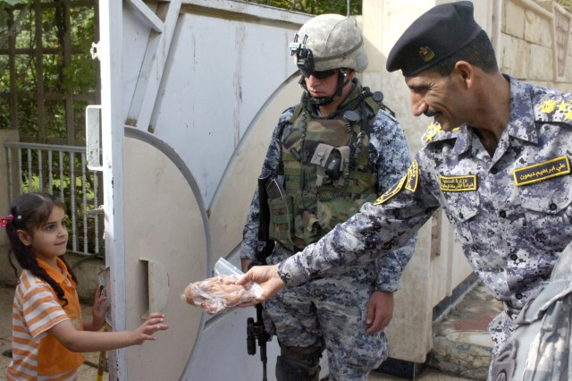 BAGHDAD - Iraqi Brig. Gen. Ali Ibraheem Dabown (right), commander of the 8th National Police Brigade, 2nd NP Division, gives an Iraqi girl a stuffed animal during Operation Asfah Ramlyah, a combined clearance operation, May 28, in the neighborhood of Sumer al-Ghadier, located in the 9 Nissan district of eastern Baghdad. NPs, along with Paratroopers assigned to the 2nd Battalion, 505th Parachute Infantry Regiment, 3rd Brigade Combat Team, 82nd Airborne Division, Multi-National Division-Baghdad, conducted the operation to disrupt insurgent activity and check the area for improvised explosive devices.